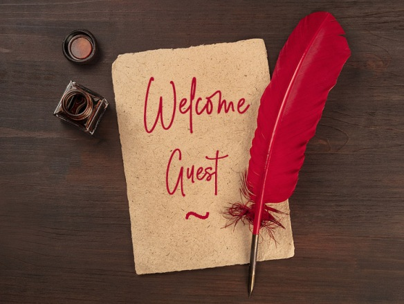 red quill pen on a piece of old parchment paper, with an ink well with words Welcome Guest in script