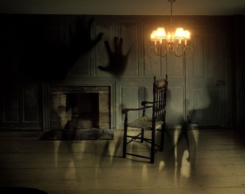 spooky deserted room with fireplace, rocker and chandelier, ghostly hands and shadows on walls
