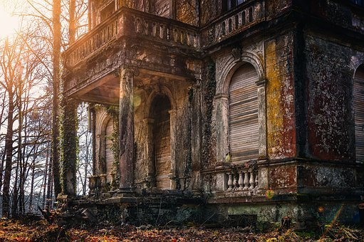 Old abandoned, boarded up two-story home in autumn woods at sunset