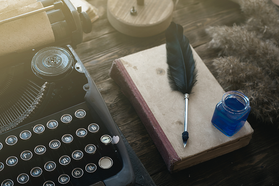 Typewriter, old book and a quill pen with a inkwell on an author desk table background.