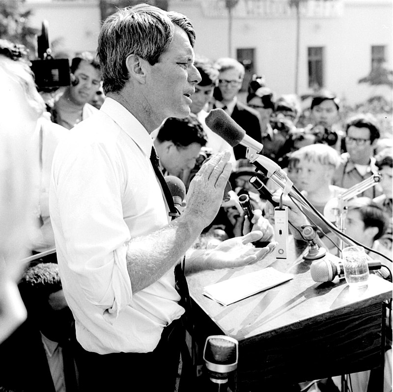 Robert F. Kennedy at podium, standing in profile, crowd gathered around him