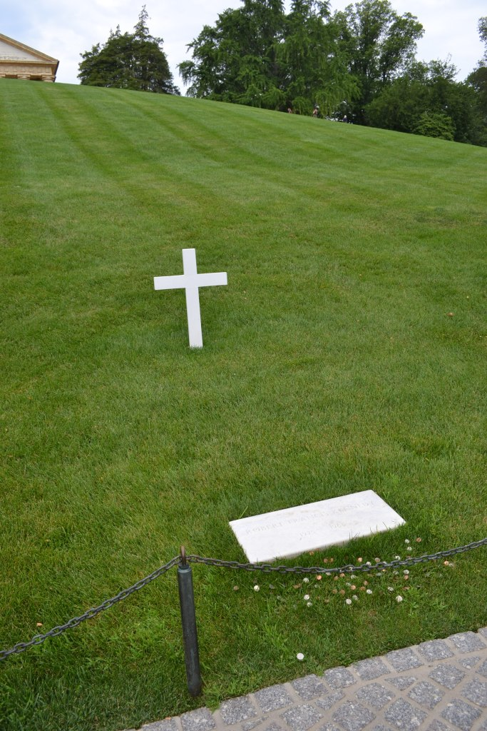 Single white cross and headstone on field of green lawn, gravesite of Robert F. Kennedy