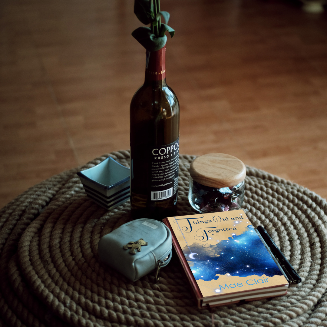 Book Things Old and Forgotten by Mae Clair set on large cool of rope on wooden floor with bottle of wine and small jars