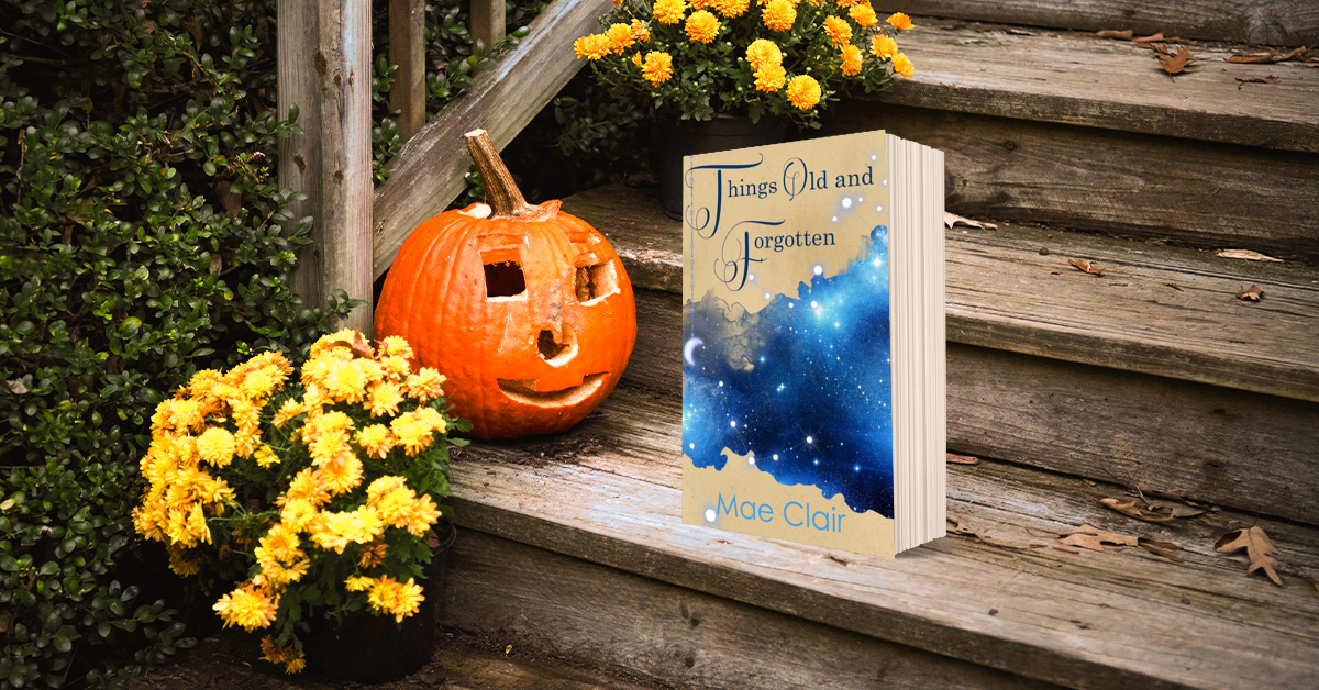 book, Things Old and Forgotten by Mae Clair on wooden steps with carved pumpkin, flowers and dried autumn leaves