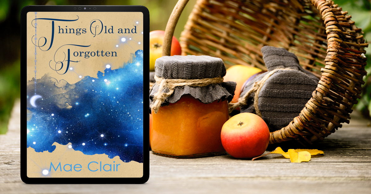 ebook Things Old and Forgotten by Mae Clair in front of wicker basket, apples and leaves, fall setting