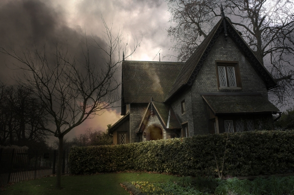 Haunted house with steep roof peaks, surrounded by shrubbery