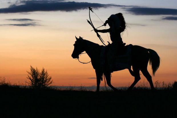 Native American with headdress and drawn bow on horse, silhouetted against evening sky